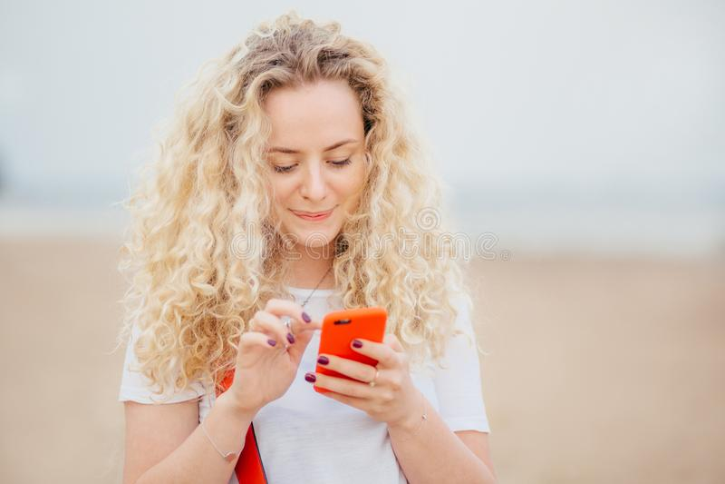 La hembra joven preciosa con el pelo espeso rizado, piel limpia sana, sostiene el teléfono elegante moderno, mensajes con los ami fotografía de archivo