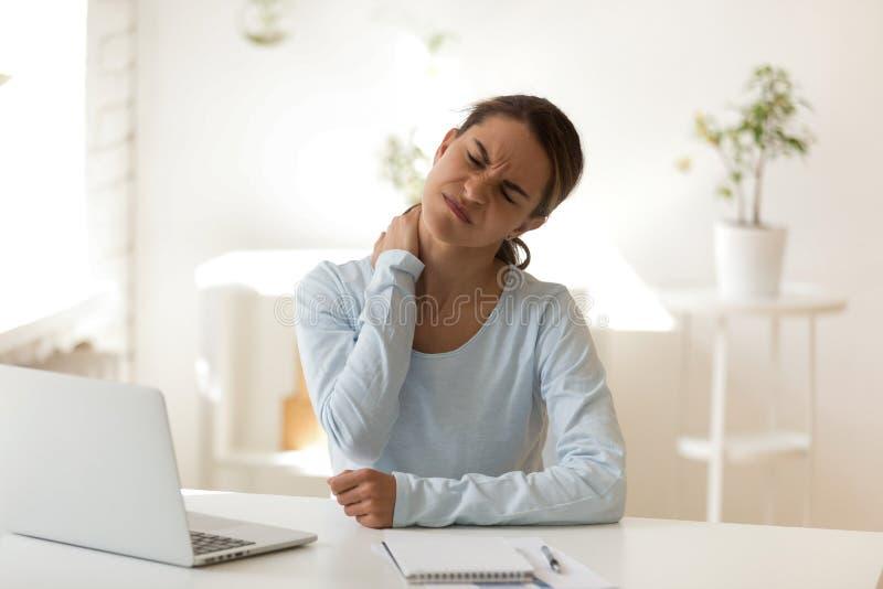 La hembra joven sufre del dolor del cuello en el lugar de trabajo imagenes de archivo