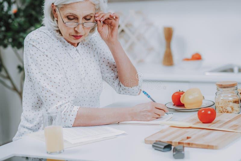 La hembra mayor atenta está escribiendo en sketchbook durante cocinar foto de archivo