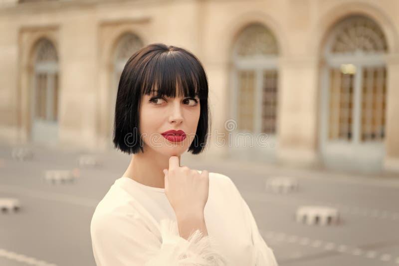La hembra misteriosa tiene idea Se?ora de moda de la muchacha con el fondo urbano al aire libre de la arquitectura del peinado de imagenes de archivo