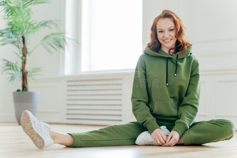 La hembra motivada deportiva demuestra la flexibilidad agradable, cuerpo delgado, estira las piernas, tiene ejercicios de los pil fotos de archivo