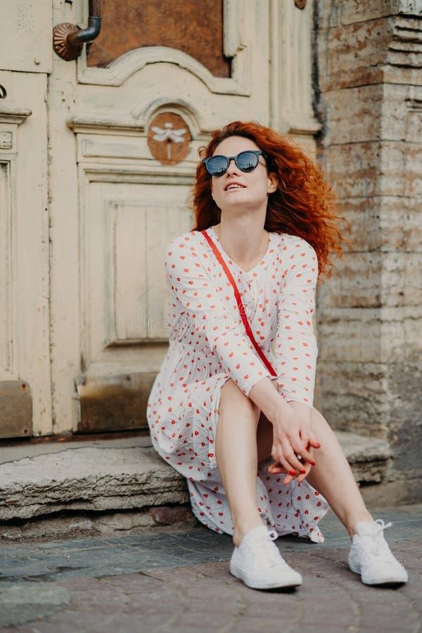 La hembra pelirroja satisfecha con el pelo rizado, lleva las gafas de sol y el vestido, presenta cerca de puerta del edificio ant imagen de archivo