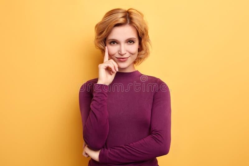 La hembra rubia bonita con sonrisa astuta, indica con el dedo índice para arriba imagenes de archivo
