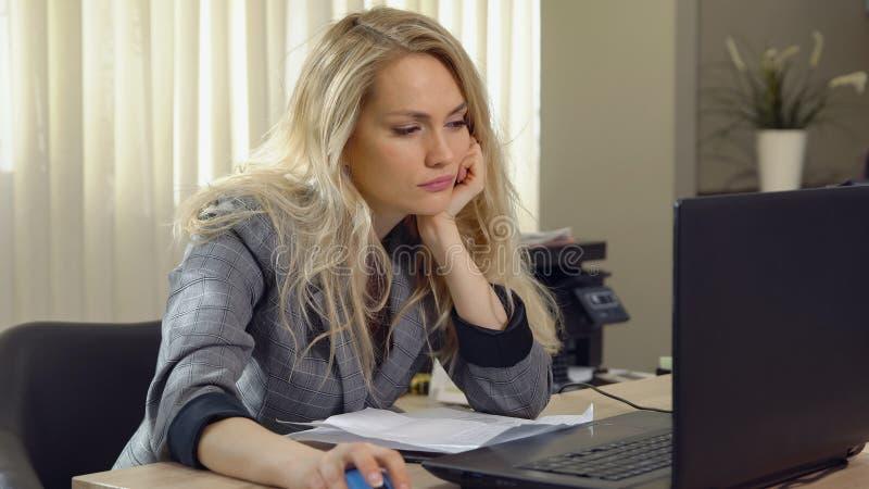 La hembra rubia cansada se cae dormido en el lugar de trabajo en oficina imagen de archivo