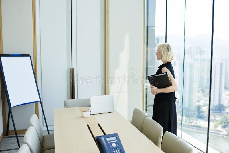 La hembra rubia está esperando al socio comercial es su oficina privada fotos de archivo libres de regalías