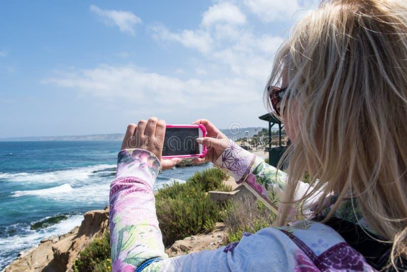 La hembra rubia toma una foto con el teléfono elegante de la playa rugosa, rocosa de La Jolla California imagenes de archivo