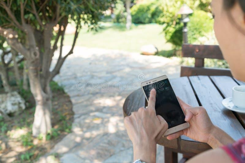 La hembra se sienta cerca por la piscina en el tiempo de verano que muestra jugar con el teléfono móvil elegante en Canakkale Tur fotos de archivo libres de regalías