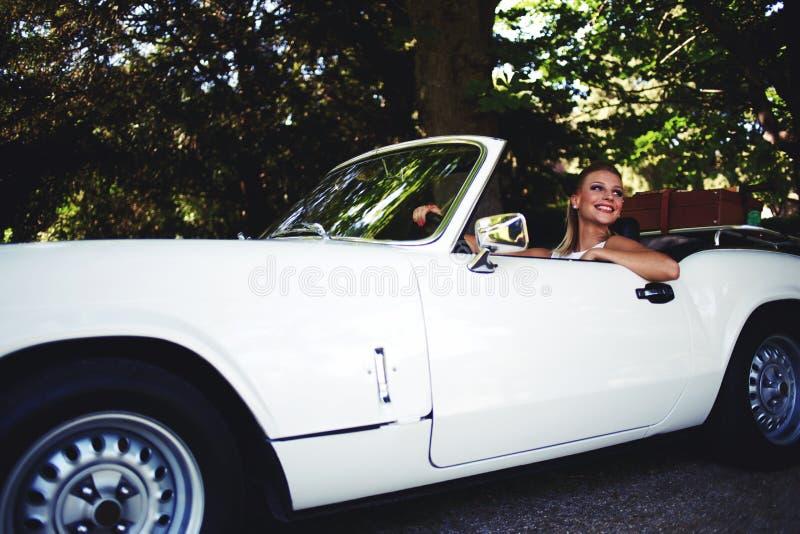 La hembra sonriente de los jóvenes se sienta en su nuevo coche convertible al aire libre que disfruta de la vida en verano fotografía de archivo libre de regalías