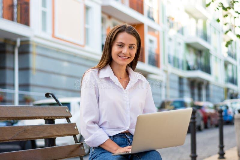 La hembra sonriente hermosa joven con un ordenador portátil asiste en un banco fotos de archivo