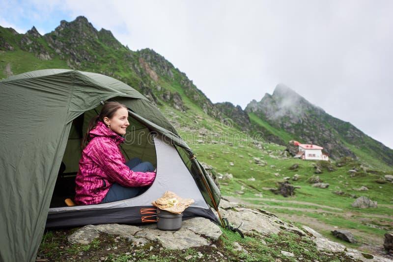 La hembra turística feliz se sienta en tienda cerca de corriente de la montaña foto de archivo libre de regalías