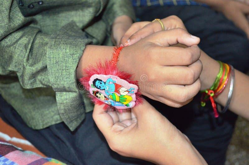 La hermana ata Rakhi en la mano del hermano en el festival de Rakshabandhan en la India imagen de archivo libre de regalías