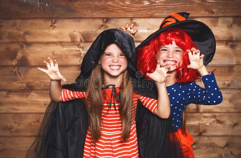 La hermana divertida de los niños hermana a la muchacha en traje de la bruja en Halloween imagen de archivo