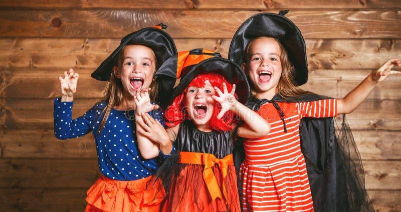 La hermana divertida de los niños hermana a la muchacha en traje de la bruja en Halloween fotos de archivo libres de regalías