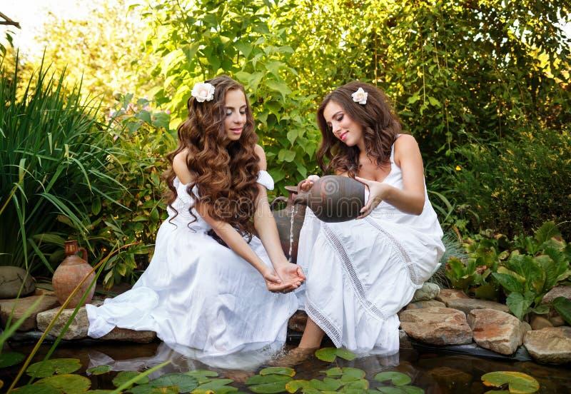La hermana vierte el agua de un jarro en su muchacha de los brazos imagen de archivo