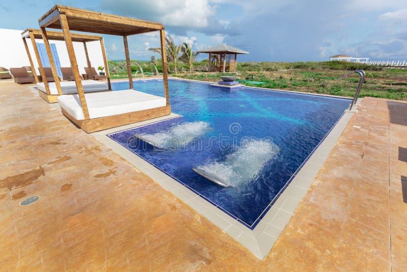 La hermosa vista de invitación que sorprende del balneario del centro turístico y la piscina con aguamarina dan masajes a camas imágenes de archivo libres de regalías