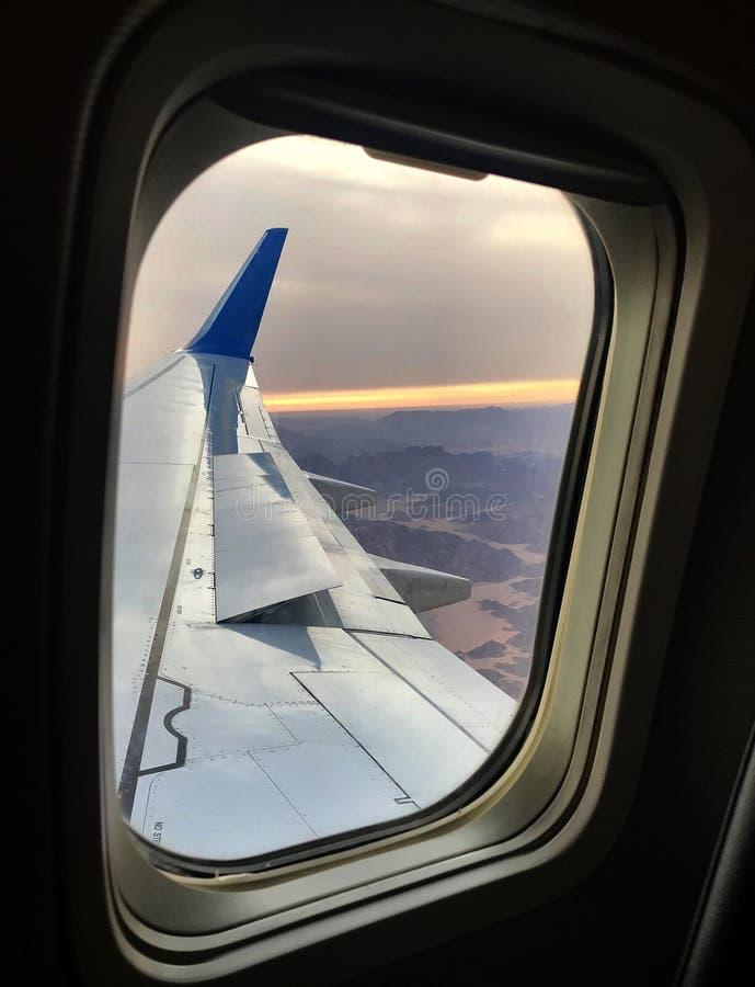 La hermosa vista de la ventana del aeroplano, ala grande de aviones muestra el marco fotos de archivo libres de regalías