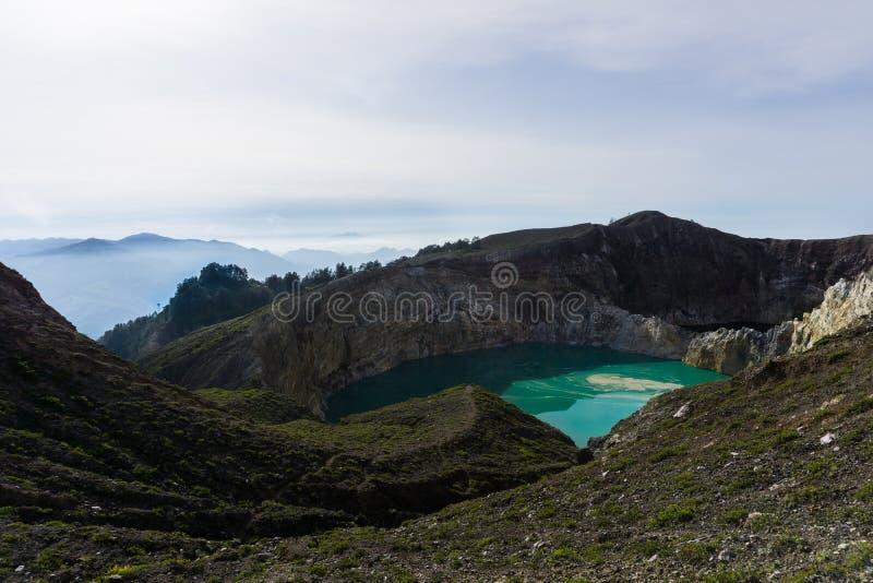 La hermosa vista del lago es colorida con un acantilado levemente brumoso El agua en el cráter del lago es Tosca y negra imagen de archivo libre de regalías