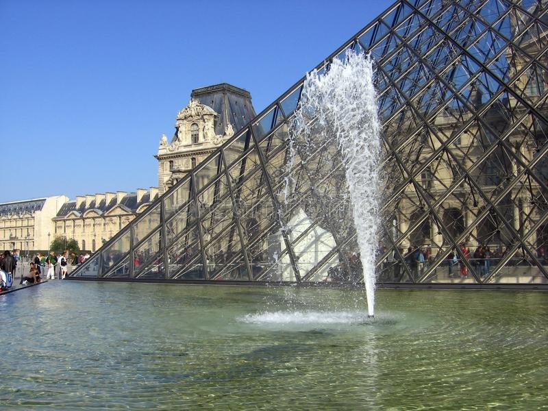 La hermosa vista del museo del Louvre esmaltó la pirámide y la fuente con el chorro de agua foto de archivo