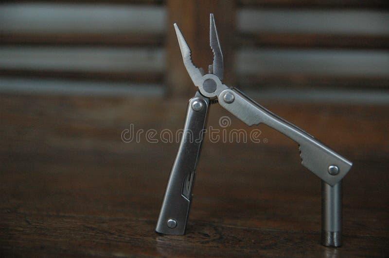 La herramienta amplió el fondo azul de las herramientas y de los alicates - práctico - cierre compacto para arriba fotos de archivo