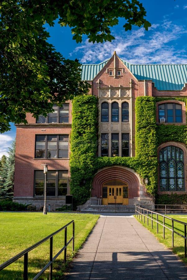 La hiedra cubrió el edificio del admin del ladrillo en Idaho fotografía de archivo libre de regalías
