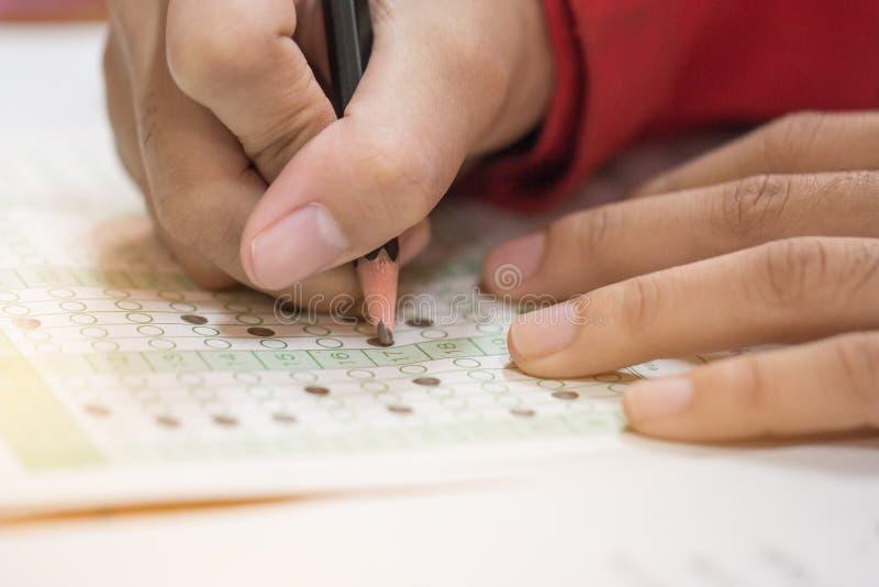 La High School o lo studente universitario passa la presa degli esami, scrivere ex fotografia stock