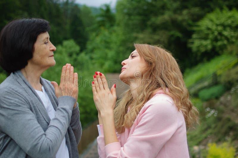 La hija adulta se disculpa con su madre fuera por el paisaje de bosques y montañas. Dos generaciones, problemas foto de archivo libre de regalías