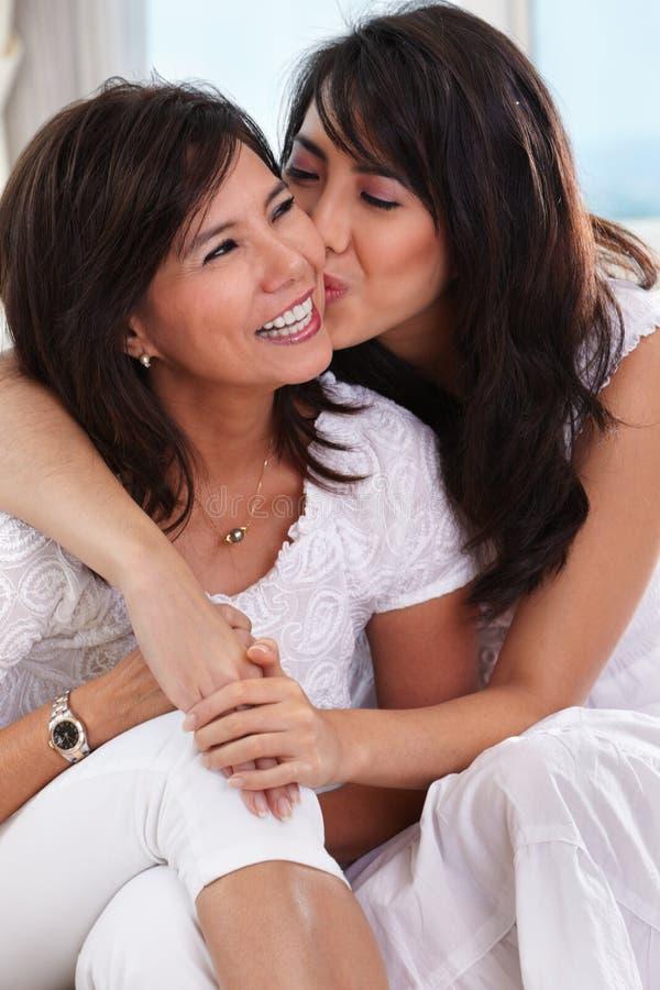 La hija besa a su madre imagen de archivo