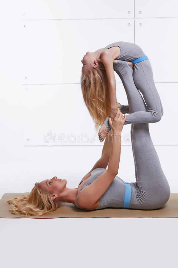 La hija de la madre que hacía el gimnasio de la aptitud del ejercicio de la yoga que llevaba los mismos deportes cómodos de la fa fotos de archivo