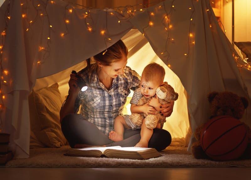 La hija de la madre y del niño con un libro y una linterna antes va fotos de archivo