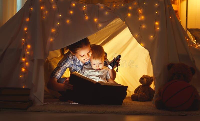 La hija de la madre y del niño con un libro y una linterna antes va foto de archivo