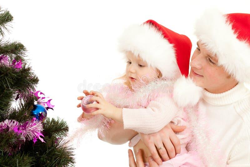 La hija de las ayudas del padre adorna el árbol de navidad imagen de archivo