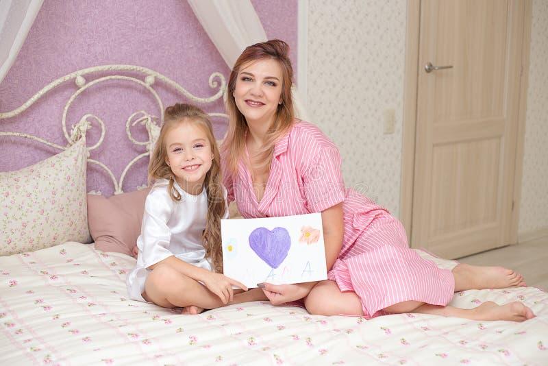 La hija del niño felicita a la mamá y le da una postal imágenes de archivo libres de regalías