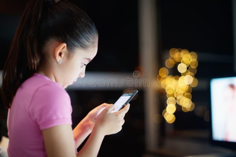 La hija desatendida escribe en red social con el teléfono fotos de archivo libres de regalías