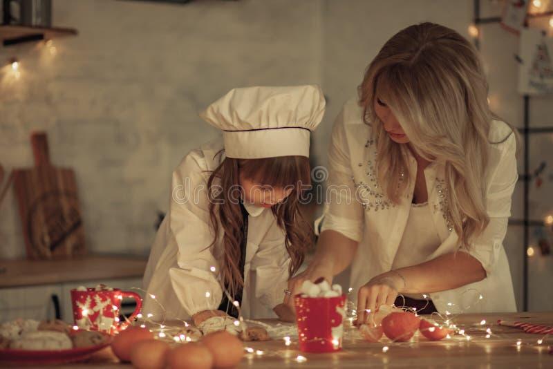 La hija en un casquillo del cocinero ayuda a su madre en la cocina fotos de archivo