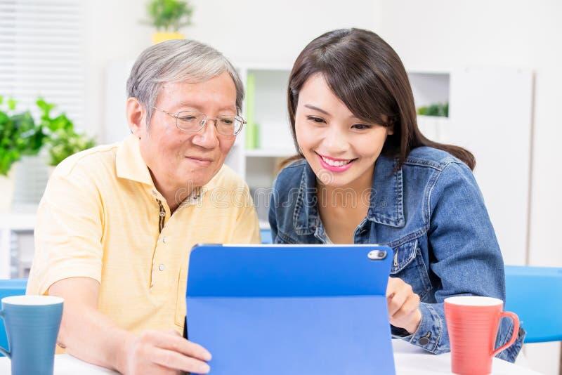 La hija enseña a la tableta del uso del padre fotografía de archivo libre de regalías
