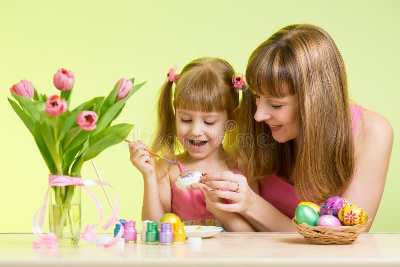 La hija feliz de la madre y del niño se prepara al día de fiesta de Pascua con los huevos del colorante del cepillo foto de archivo libre de regalías
