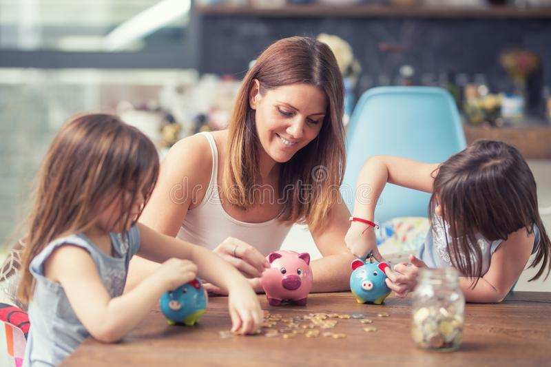 La hija feliz de la mamá de la familia ahorra ahorros de la inversión del futuro de la hucha del dinero imágenes de archivo libres de regalías