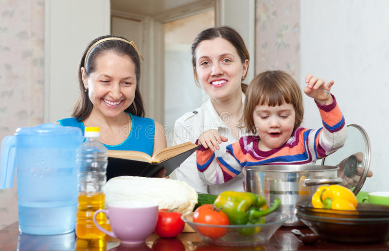 La hija madura de la mujer y del adulto con el bebé cocina verduras imagen de archivo libre de regalías