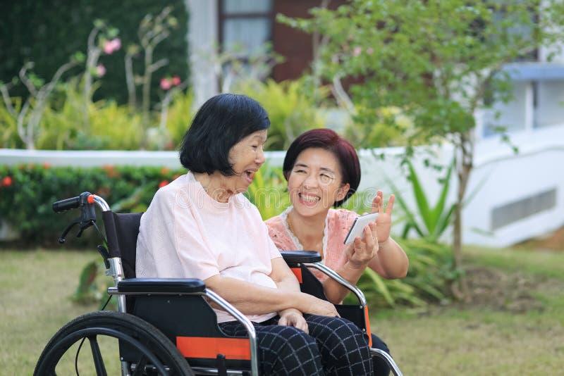 La hija que cuida para la mujer asiática mayor, hace el selfie, feliz, imagen de archivo libre de regalías