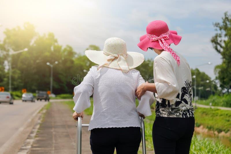 La hija toma a cuidado la mujer mayor que camina en la calle imagen de archivo