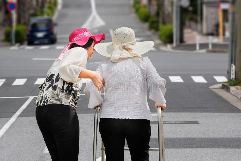 La hija toma a cuidado la mujer mayor que camina en la calle fotografía de archivo