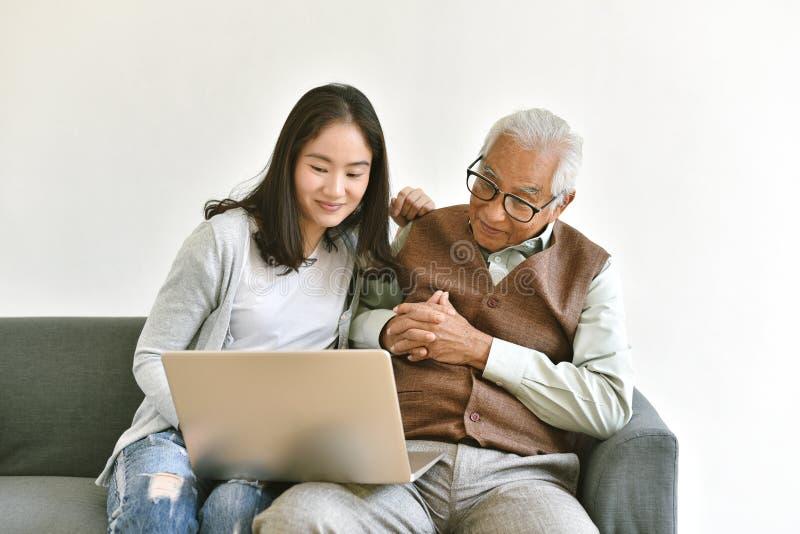La hija y el padre mayor usando el ordenador portátil juntos, gente mayor pasan tiempo que aprende utilizar medios sociales y dig imagen de archivo