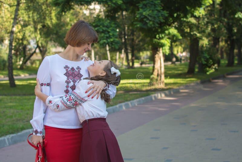 La hija y la mamá se colocan y abrazan en camisas bordadas fotografía de archivo libre de regalías