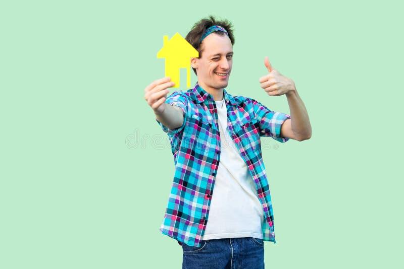 La hipoteca es buena Hombre joven centellante positivo en la camisa a cuadros que sostiene la pequeña casa de papel amarilla y pr fotografía de archivo