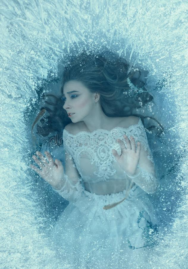 La historia de una bella durmiente La muchacha despertó en la parte inferior de una nadada congelada del lago, de los pescados y  imagen de archivo