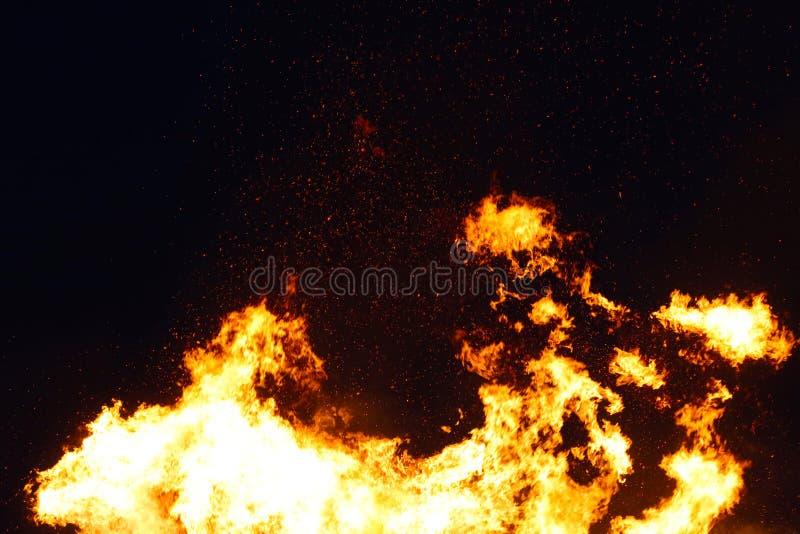 La hoguera grande, quemando y brillando intensamente con las llamas suaves, chispea los agains que vuelan el cielo oscuro Noche d fotografía de archivo libre de regalías