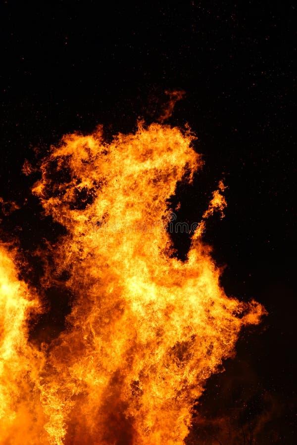 La hoguera grande, quemando y brillando intensamente con las llamas suaves, chispea los agains que vuelan el cielo oscuro Noche d imagenes de archivo