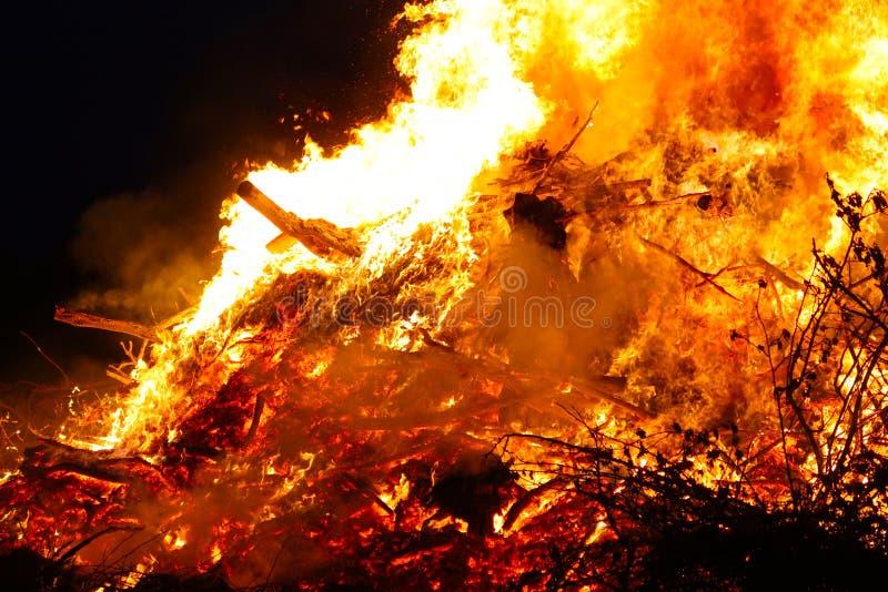 La hoguera grande, quemando y brillando intensamente con las llamas suaves, chispea los agains que vuelan el cielo oscuro Silueta foto de archivo