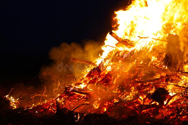 La hoguera grande, quemando y brillando intensamente con las llamas suaves, chispea los agains que vuelan el cielo oscuro Silueta fotografía de archivo