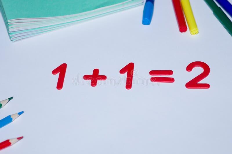 La hoja blanca dice 1 1=2 Endecha al lado de los lápices y de los cuadernos foto de archivo